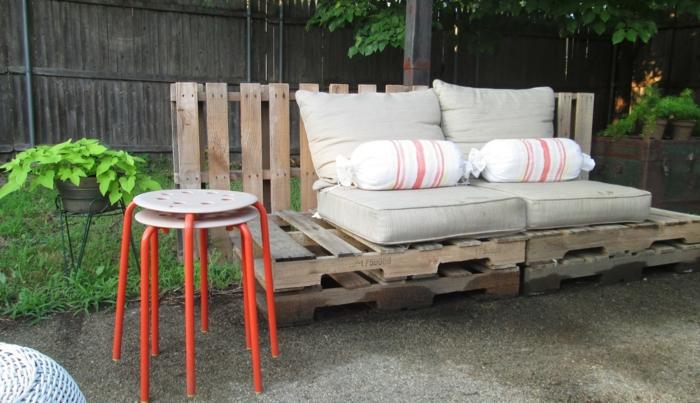 banc en palette, canapé en palette, salon de jardin palette, tabourets métal ronds en blanc avec des pieds en rouge, jardin aménagé avec des objets de récupération
