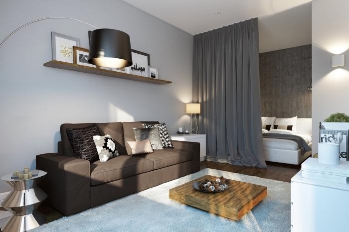 modèle d'aménagement petit appartement avec séparation de pièce en rail de rideaux longs et meubles de bois massif