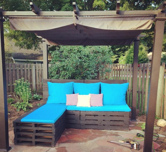 coussin salon de jardin palette bleu, canapé d angle palettes et pergole en bois et métal dans un jardin
