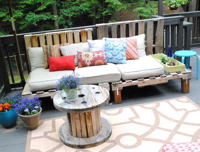 exemple de salon de jardin palette avec un canapé palette de bois avec coussin d assise gris et coussins décoratifs colorés, table touret, deco terrasse pots de fleurs