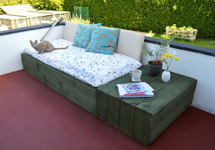 canapé en palette de bois avec des planches vert olive, coussin d assise blanc et coussins décoratifs gris et bleu, pots de fleurs