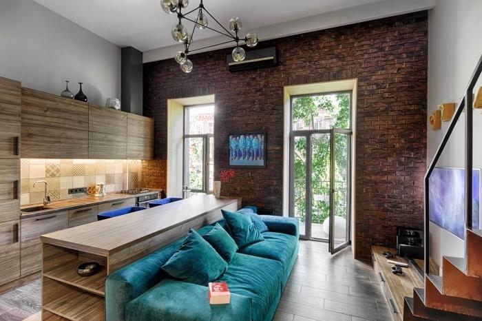 mixer les styles dans le décor avec mur en briques rouges combinés avec meubles de bois foncés et canapé turquoise