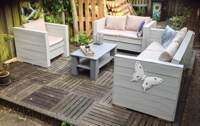 fauteuil et canapés de jardin en bois et table basse en palette facile, coussins rose sur une terrasse en bois