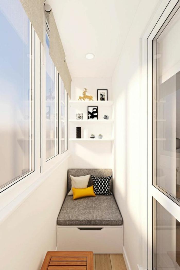 terrasse en longueur, idée déco appartement, canapé avec matelas et coussin gris clair et mini coussins en jaune, blanc et noir, étagères blanches avec des tableaux et des objets déco
