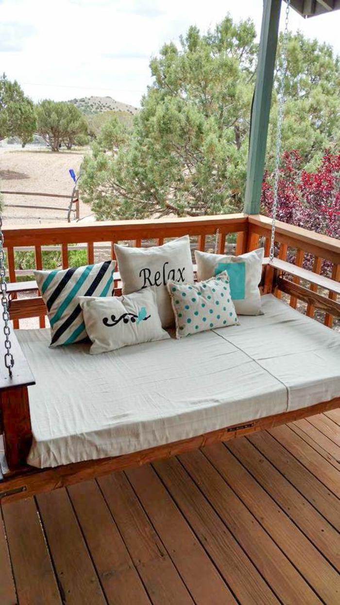 salon de jardin en palette, canapé en palette balançoire, coussins de taille diverse avec des inscriptions, des rayures en couleurs pastels et des pois