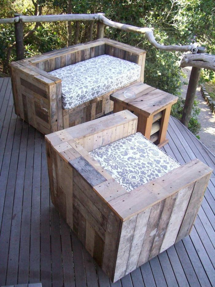 fauteuil palette, deux pièces en bois clair et plus foncé, table carrée avec des pieds hauts, coin sous la couronne d'un arbre pour avoir de l'ombre