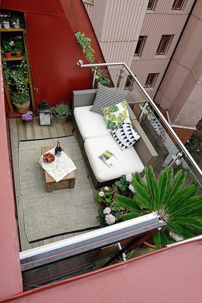 idee amenagement terrasse, decoration jardin terrasse, niche en bois pour les pots de fleurs, garde-corps en verre transparent trempé, tapis rectangulaire en réséda avec table en palettes avec une mini-nappe, une bouteille de champagne et des fraises