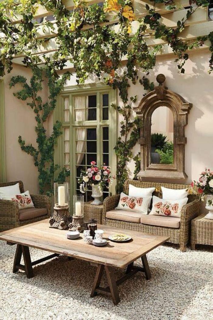 décorer son jardin en style shabby chic, miroir classique au mur, canapés et fauteuils en rotin beige clair, pergola recouverte de plantes rampantes, fenêtre de maison en vert pistache