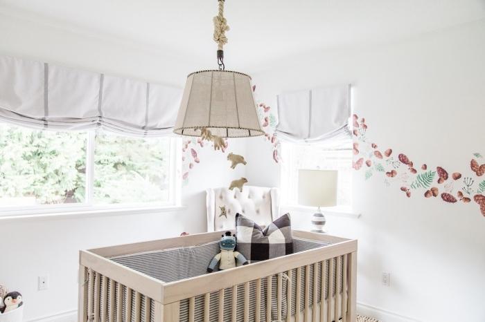 deco chambre aux murs blancs avec grandes fenêtres et mobilier de bois clair, lit bébé au centre de la pièce avec couverture grise et coussins