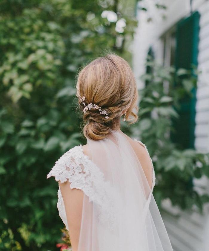 modele de coiffure femme chignon bas sur carré long avec decoration de fleurs artificielles, robe de mariée dentelle