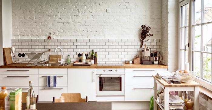 déco de style rustique dans une cuisine aménagée en longueur avec armoires blanches et comptoir de bois massif