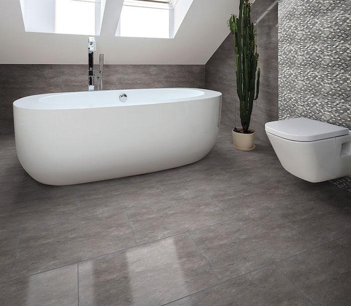 salle de bain mansardée avec baignoire ilot blanche ovale et carrelage gris marbré brillant