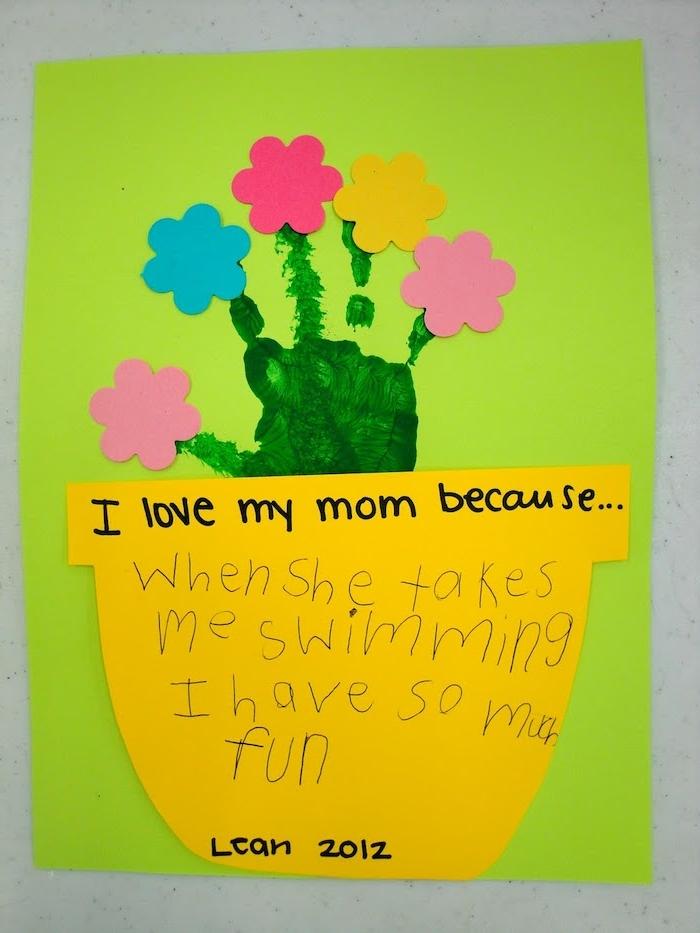un pot de fleur en papier jaune avec message pour maman et empreinte de main verte, arbre avec des fleurs en papier colorées
