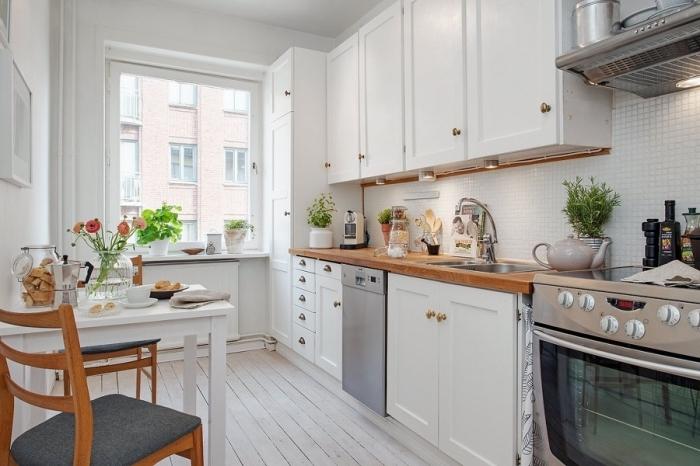 comment aménager une petite cuisine avec meubles blancs à poignées dorées et comptoir de bois marron foncé