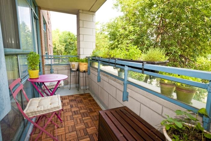 jolie décoration de terrasse ou balcon avec carrelage de sol à imitation bois et meubles table et chaise en rose
