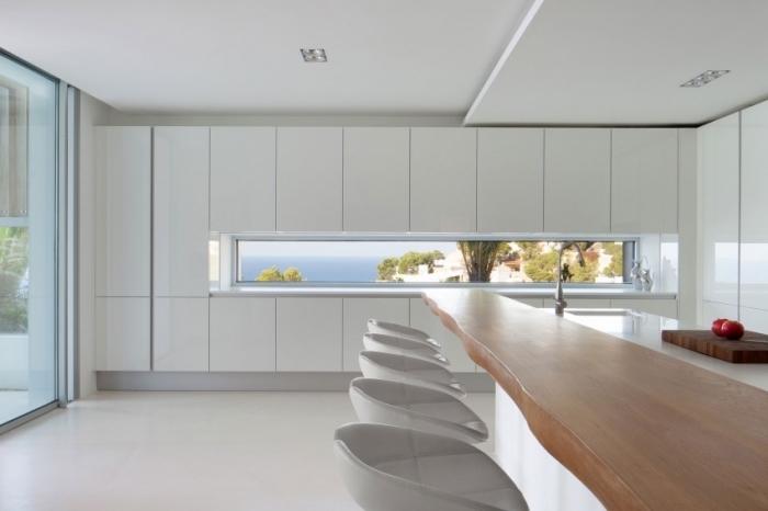 intérieur design moderne et épuré avec meubles blancs sans poignées et un modèle d'ilot central en comptoir de bois massif