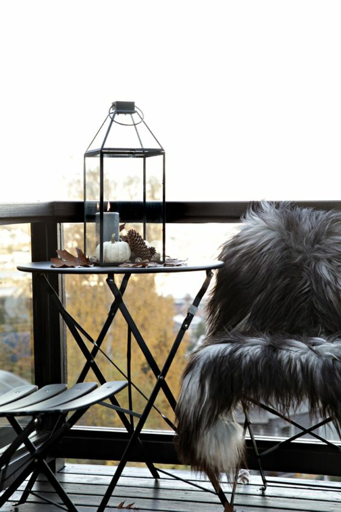 deux chaises en bois et en métal noir, idee amenagement terrasse, lanterne en métal noir avec bougie grise, sol recouvert de bois noir, couverture de chaise en fausse fourrure poil long en blanc et noir