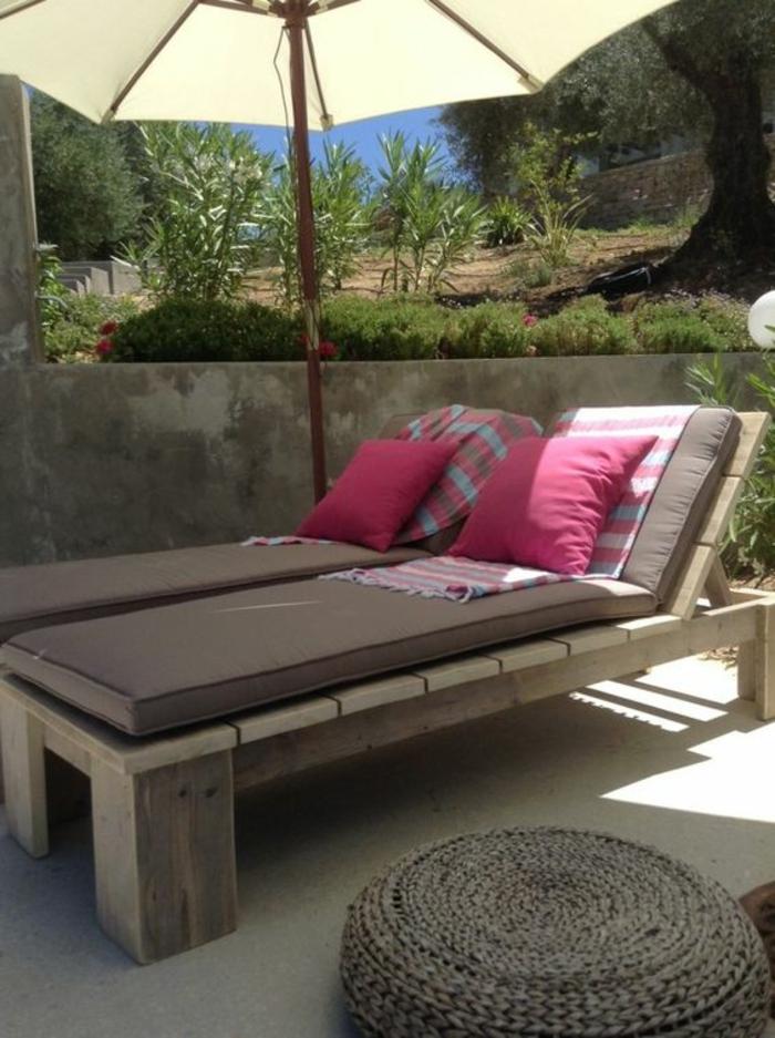 salon de jardin palette, chaises-longues en bois marron avec coussins fuchsia, parasol en couleur ivoire, tabouret en style marocain en forme ronde en osier tressé