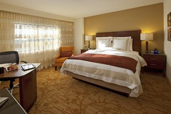 belle chambre parentale à déco zen, tapis à motifs floraux, mur vert, grand bureau de bois solide