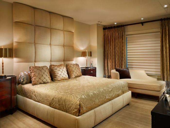 jolie chambre à coucher en couleurs neutres, rideaux lourds ocre, sofa beige, chevet en bois rouge