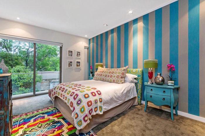grande chambre enfant avec baie vitrée, tapisserie gris et bleu et tapis coloré du pérou
