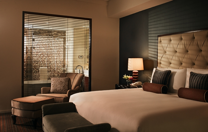 mur marron, lit couleur taupe, tête de lit capitonné, fauteuil coulaue taupe, coussins déco