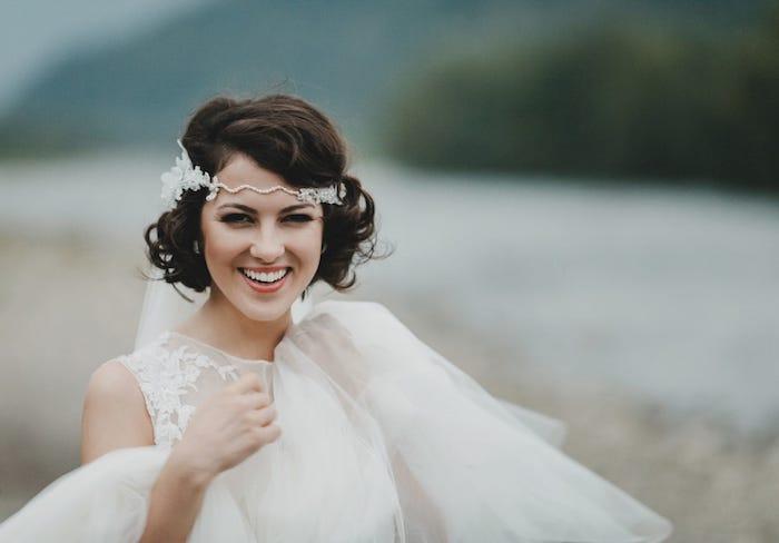 coiffure de mariée style année 20, cheveux buclés et volume sur le dessus, serre tête blanche à otifs fleuris