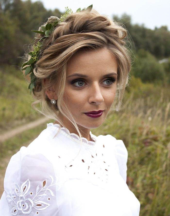 coiffure de mariage boheme chic avec des mèches ondulées attachées en haut de la tete et couronne de fleurs verte, robe de mariée transparente