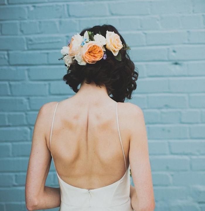 robe de mariée dos nu avec carré plongeant bouclé accessoirisé de fleurs, coiffure cheveux carré boheme
