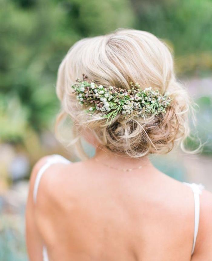 chignon mariage boheme chic style flou accessoirisé de fleurs naturelles, cheveux blond bouclés