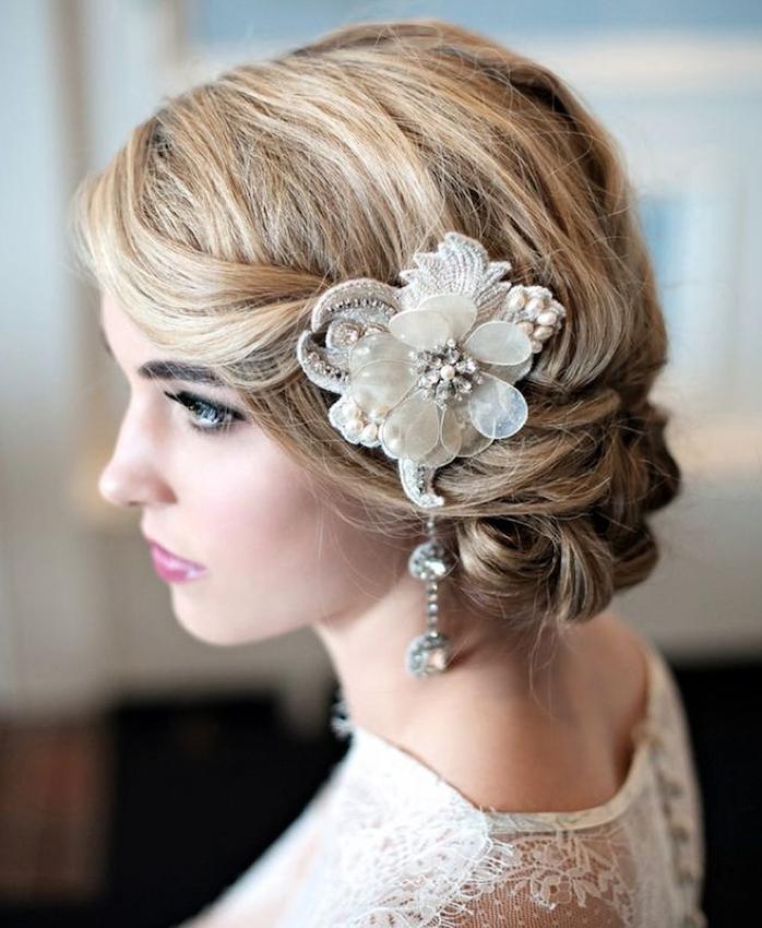 fleur décorative sur le coté de la tete et chignon mariage bas sur cheveux bouclés volumineux blond
