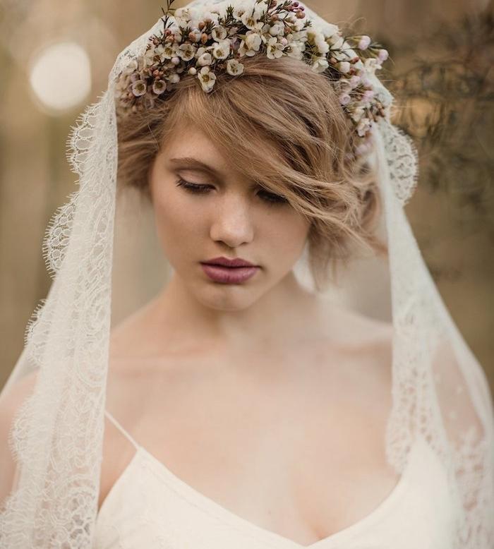 idee coiffure mariage cheveux mi long avec des boucles, volume sur le dessus et mèche de coté, couronne de fleurs blanches, voile de mariée dentelle
