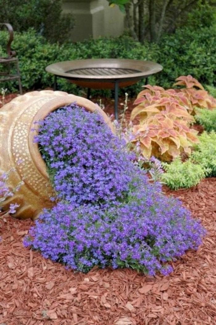 amphore renversée utilisée comme élément déco, des fleurs en bleu indigo sortent de son intérieur, jardin paysager, amenagement exterieur
