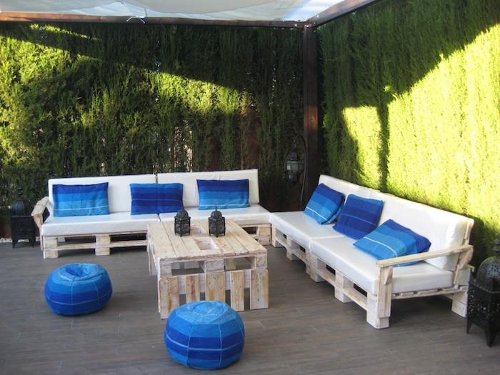 meubles de jardin en palettes canapés en palettes blanchis avec coussins d assise blancs et coussins décoratifs et poufs bleus, table basse palette, mur végétal