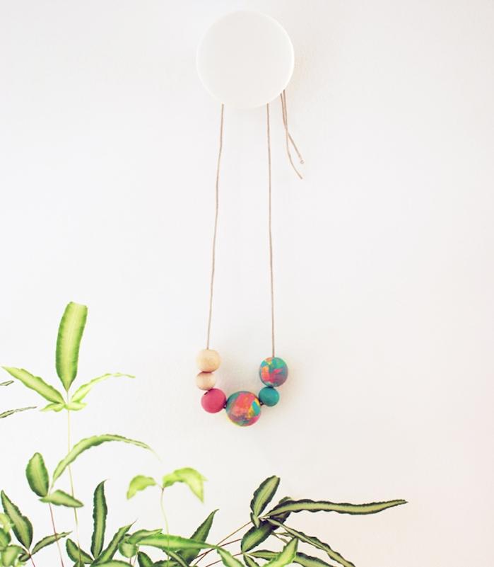 un collier avec des perles en bois colorées accroché sur un mur, diy fete des meres facile pour fabriquer un accessoire femme