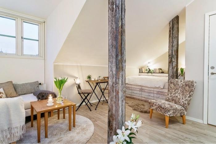 modèle d'aménagement studio 25m2 sous pente avec colonne de bois et petite fenêtre, ambiance cocooning avec tapis et plaid beige
