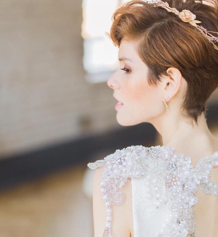 coupe pixie avec mèche de coté et accessoire couronne aux fleurs artificielles fines, couleur cheveux chatain clair, robe de mariée aux perles