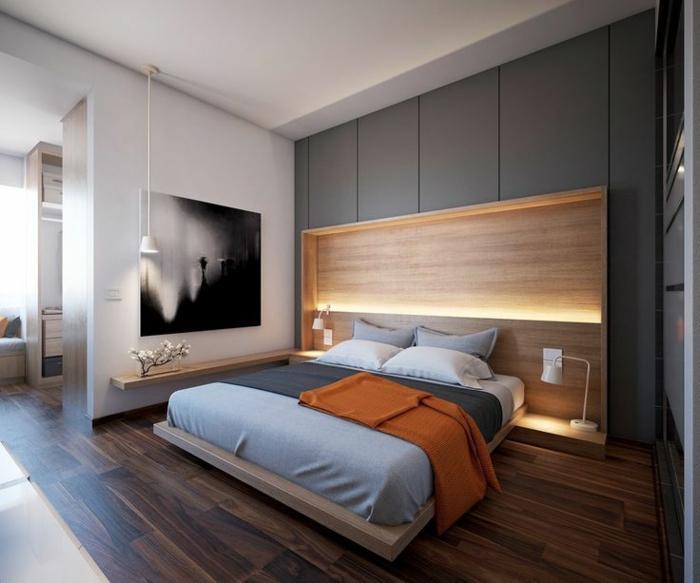 lit plateforme beige, matelas gris, sol en bois, tête de lit avec rangement et deux lampes de chevet