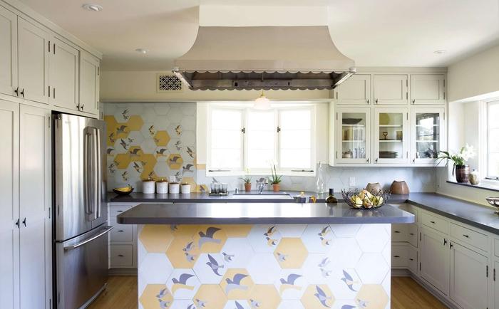 cuisine blanche et grise fonctionnelle et conviviale égayée par des carreaux de ciment hexagonaux motif oiseaux sur le mur de crédence et sur la façade de l'îlot central