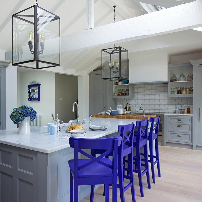 une cuisine grise et blanche de style rustique contemporaine équipée d'un îlot central par accentué par des chaises bleu de cobalt et des suspensions lanternes en verre et laiton