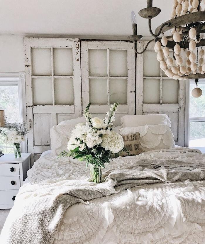 portes en bois recyclées aspect brut avec linge de lit blanc et plaid gris, bouquet de fleurs blanches, lustre élégant, style campagne chic
