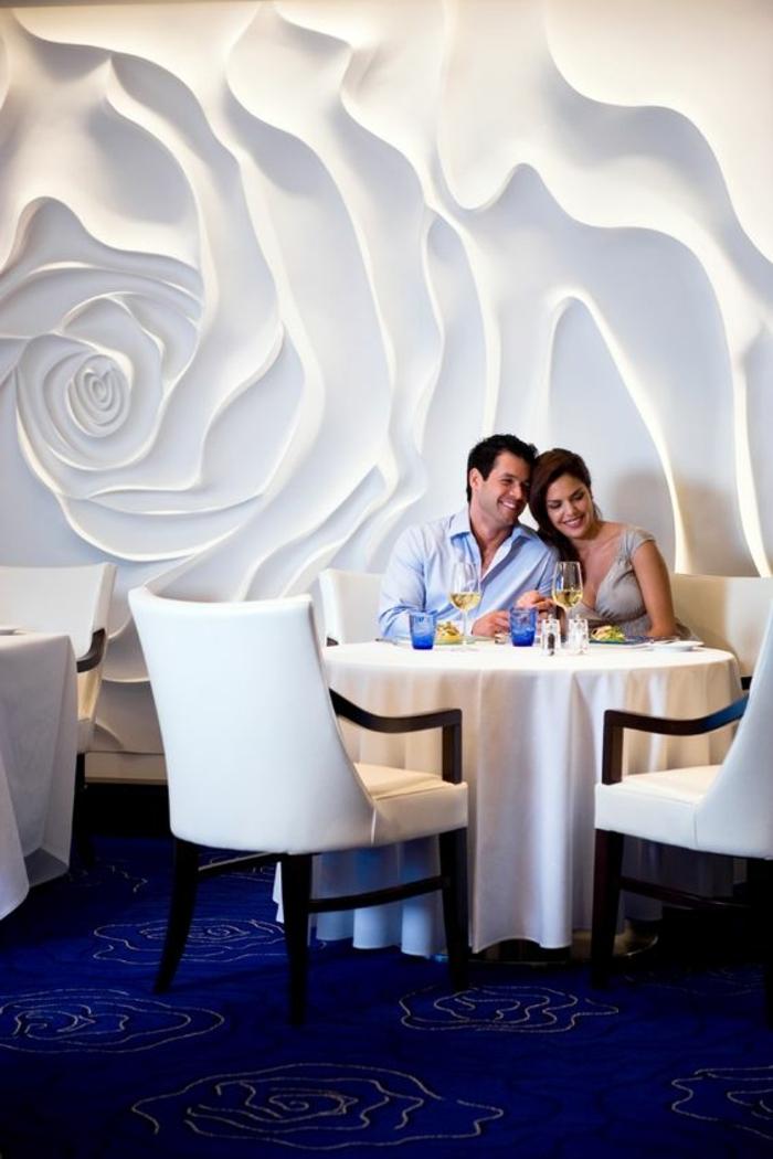idee deco mur, sticker mural en 3D, motifs grandes roses blanches, local restaurant chic, aménagement avec des meubles en bois laqué noir et du simili cuir blanc, moquette bleu roi avec des motifs délicats roses en blanc