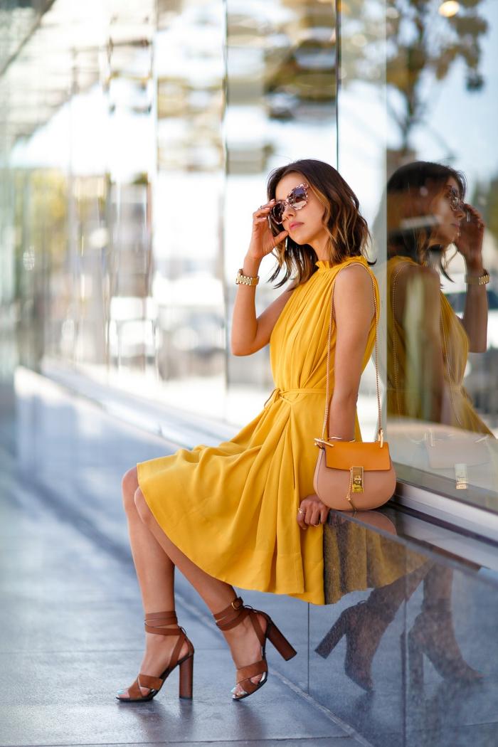 robe de soirée midi longue jaune portée avec un sac bicolore et hautes sandales beiges