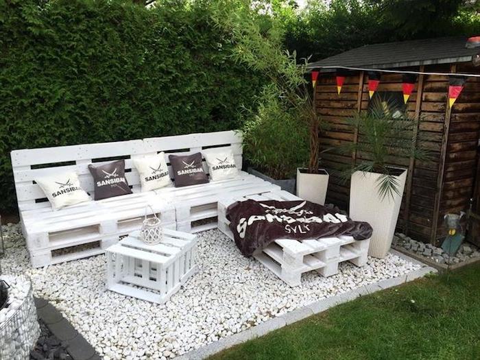 idée originale de salon de jardin palette avec canapé d angle repeint en blanc, table basse palette sur gravier blanc, mur végétal