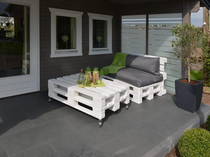 deco terrasse couverte sous pergola moderne avec fauteuil en palette blanchi et table palette basse en blanc à roulettes