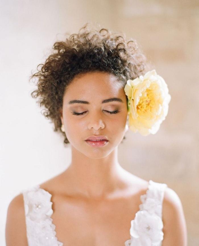 coiffure afro femme aux cheveux crépus accessoirisés d une large rose jaune de coté de la tete, robe de mariée blanche fleurie