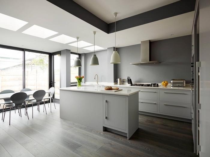 cuisine ilot central peint gris mat avec comptoir en quartz blanc qui se fond dans le décor épuré en tons neutres
