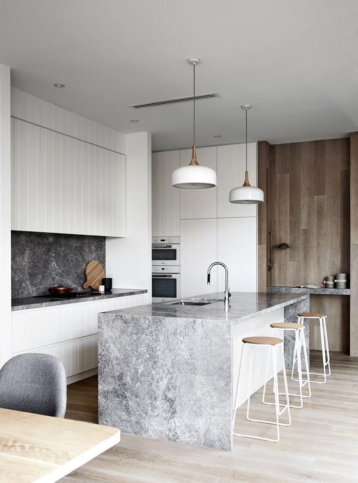 ambiance nordique et contemporaine dans une cuisine moderne grise qui joue sur les différentes finitions
