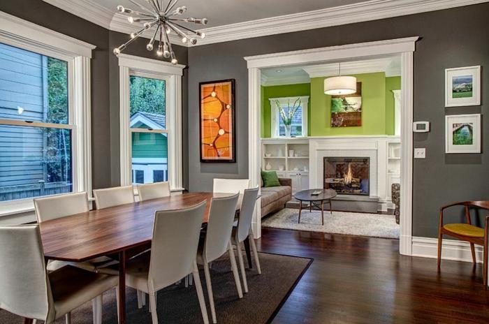 grande table rectangulaire avec des chaises blanches, peintures abstraites, mur vert et manteau de cheminée blanc