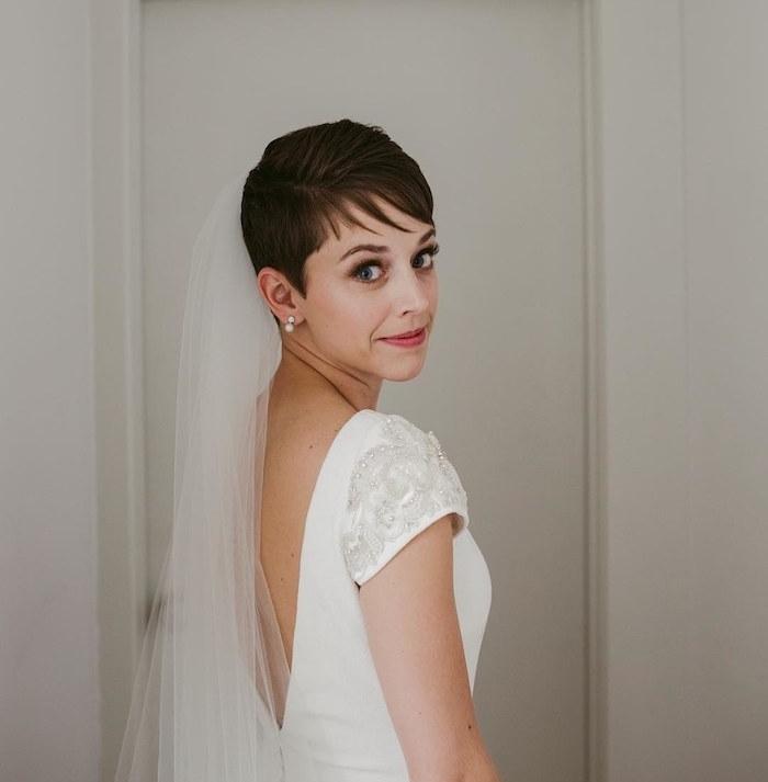 coiffure pixie lisse avec frange effilé latérale et robe de mariée à manches et dos nu, voile de mariage longue